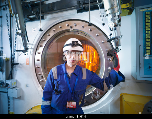 Portrait of engineer with fuel rod handling machine in nuclear power station - Stock Image