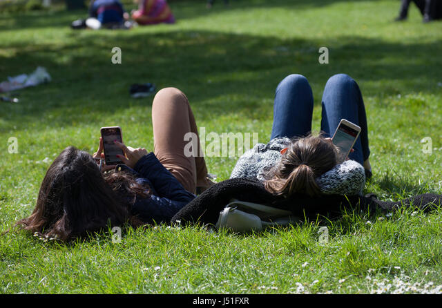 Two girls lying in the grass in a park sending and reading text messages and not speaking with each other on a sunny - Stock Image