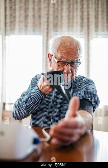 Senior man controlling his blood pressure at home - Stock Image