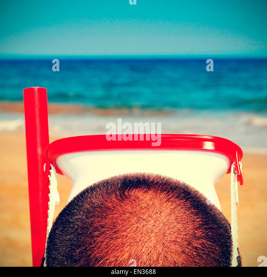 picture from the back of a man wearing a diving mask and a snorkel on the beach, with a retro effect - Stock-Bilder