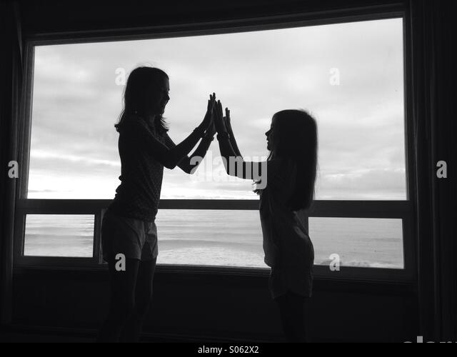 Two girls in silhouette high five in front of a picture window. The image is black and white. - Stock-Bilder