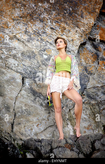 Young woman standing next to a cliff at the beach - Stock Image