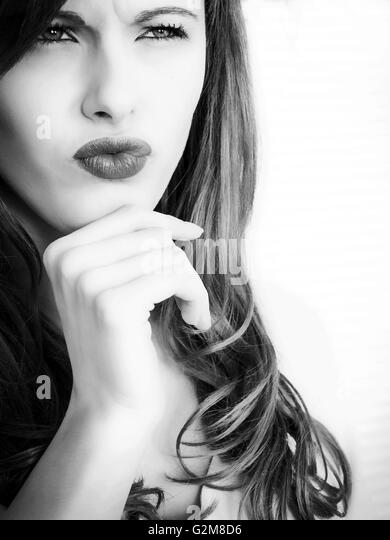Black and White Portrait of a Tense Pensive Young Woman Looking Thoughtful and Concerned - Stock Image
