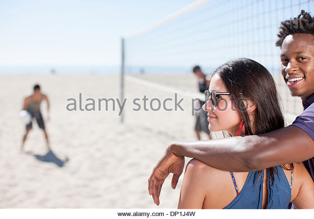 Couple standing on beach volleyball court - Stock Image