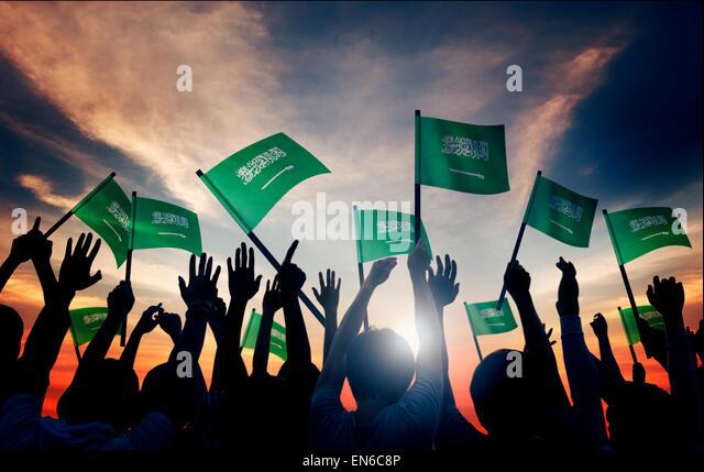 Silhouettes of People Holding Flag of Saudi Arabia - Stock Image