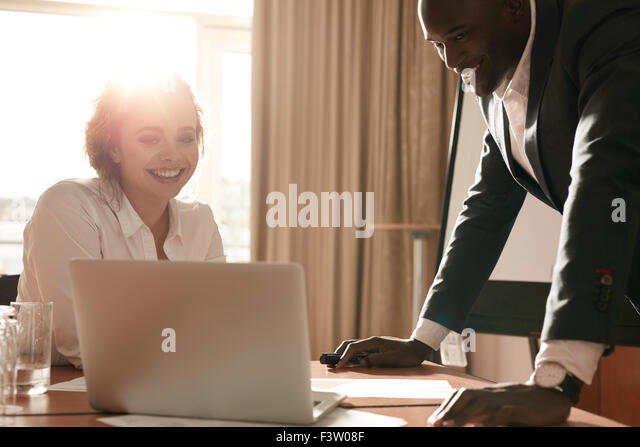 Portrait of happy young business team working together on laptop. Businessman and businesswoman meeting in conference - Stock Image
