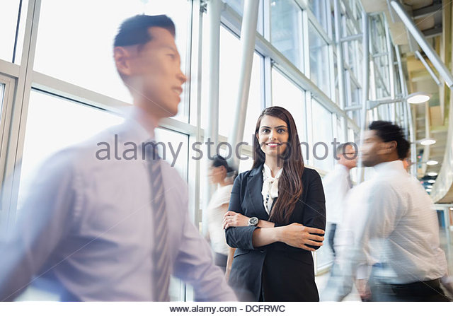 Confident businesswoman standing among busy co-workers - Stock Image