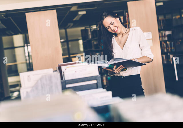 Beautiful woman reading books in a library and smiling - Stock Image