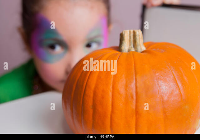 Little cute girl behind pumpkin after making facepaint for halloween party - Stock Image