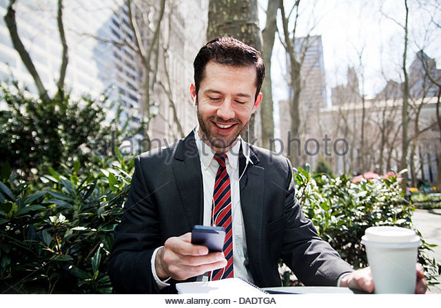 Businessman looking at smartphone and smiling - Stock-Bilder