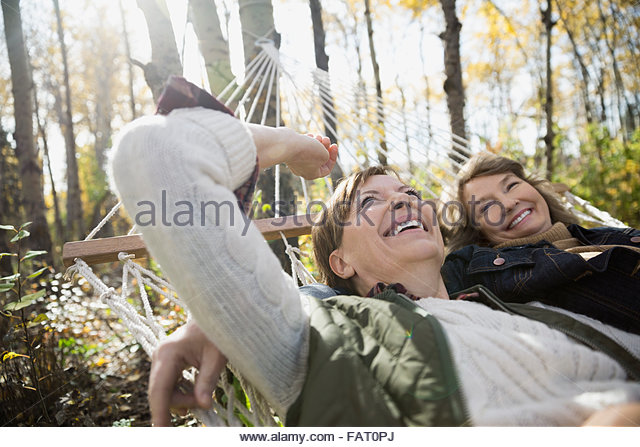 Carefree friends laying in hammock - Stock Image