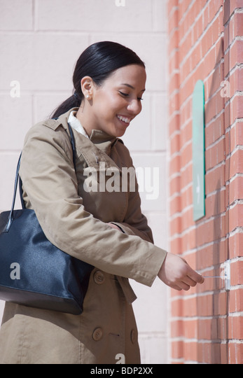 Hispanic woman inserting a bank card into the bank access slot - Stock-Bilder