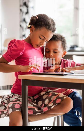 Children using tablet computer in classroom - Stock Image