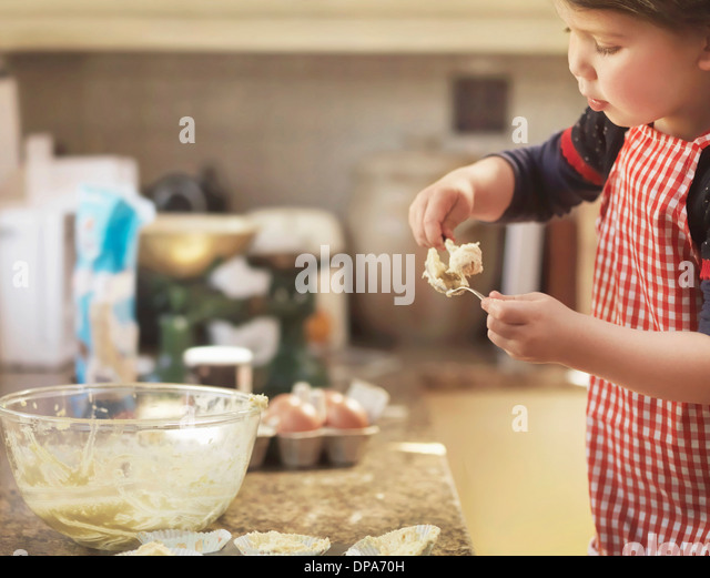 Child holding spoon with cake mix - Stock-Bilder