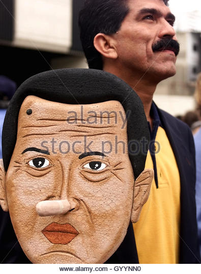 Rafael Narvaez, a protester in an anti-government demonstration,  carries a placard bearing a caricature of Venezuelan - Stock Image