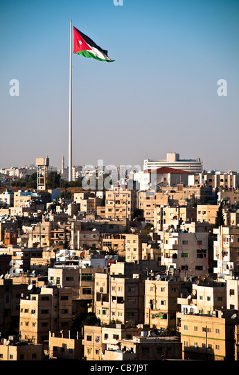 view of city of Amman with giant jordanian flag and blue sky in background - Stock Image