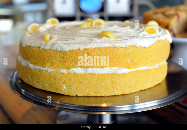 Lemon sponge cake complete with lemon icing in a deli shop window - Stock Image