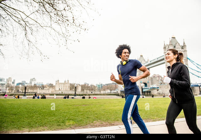 A young couple jogging together past Tower Bridge in London. - Stock-Bilder