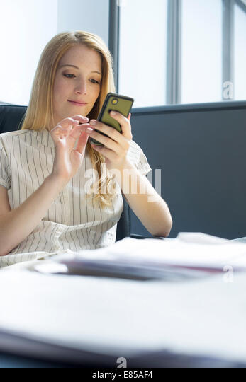College student using smartphone during study break - Stock Image