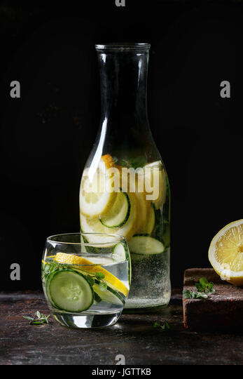 Citrus cucumber sassy sassi water for detox in glass bottle on dark black background. Clean eating, healthy lifestyle - Stock Image