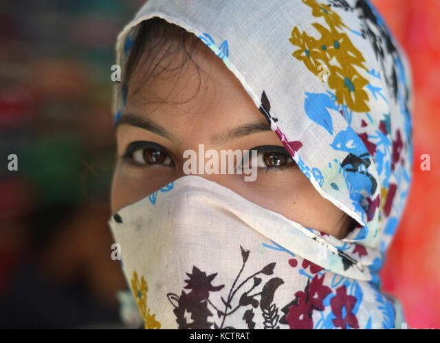 Young Assamese beauty with oriental eyes, covering her hair and face with a trendy, secular floral headscarf at - Stock Image