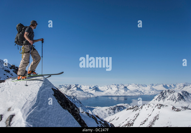 Man on skis at top of mountain in East Greenland - Stock Image