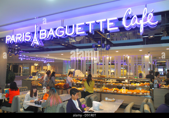 Singapore Orchard Road Ion Orchard mall complex upscale shopping Paris Baguette Cafe restaurant dining Asian woman - Stock Image