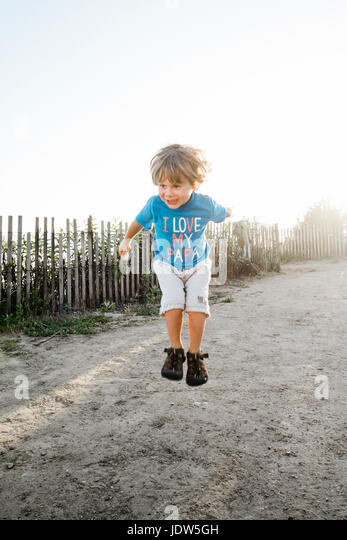 Boy jumping at coast - Stock-Bilder