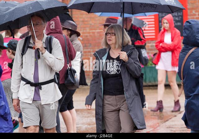Umbrellas in the rain at the Maverick Americana music festival - Stock Image