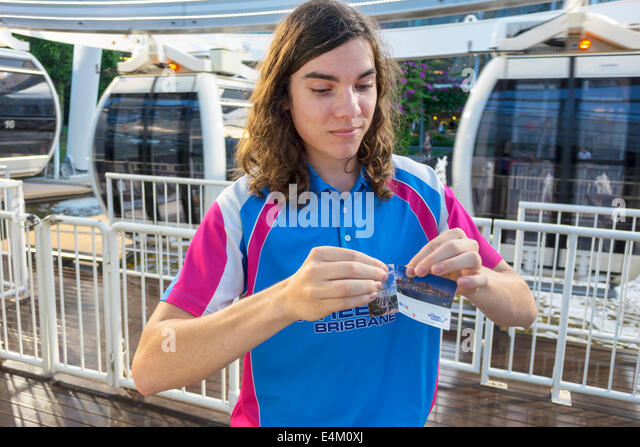 Brisbane Australia Queensland Southbank The Wheel Ferris wheel teen boy job tearing ticket ride long hair - Stock Image