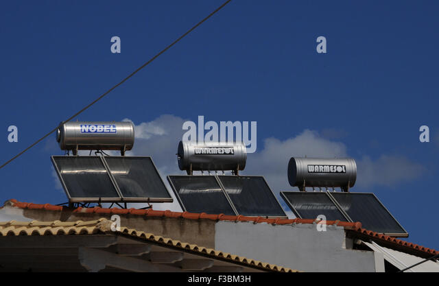 Solar water heaters on a roof top in the small Greek village of Giolova in the Peloponnese. - Stock Image