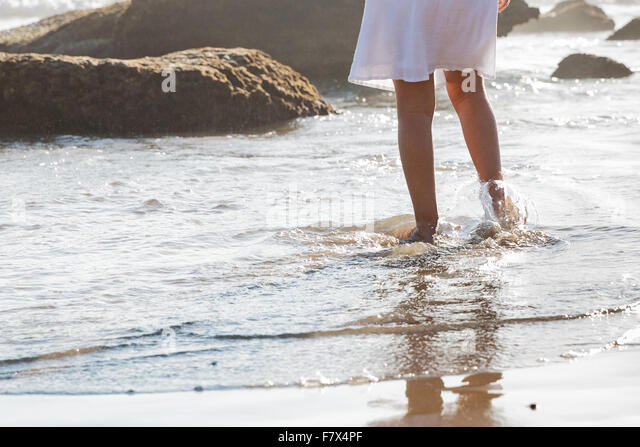 Girl walking in the surf on the beach - Stock Image