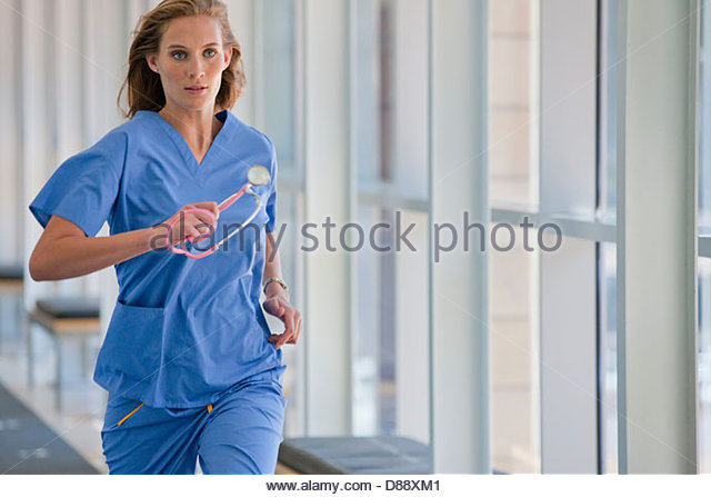 Nurse running down hospital corridor - Stock Image