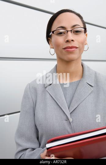 African businesswoman holding binder - Stock-Bilder