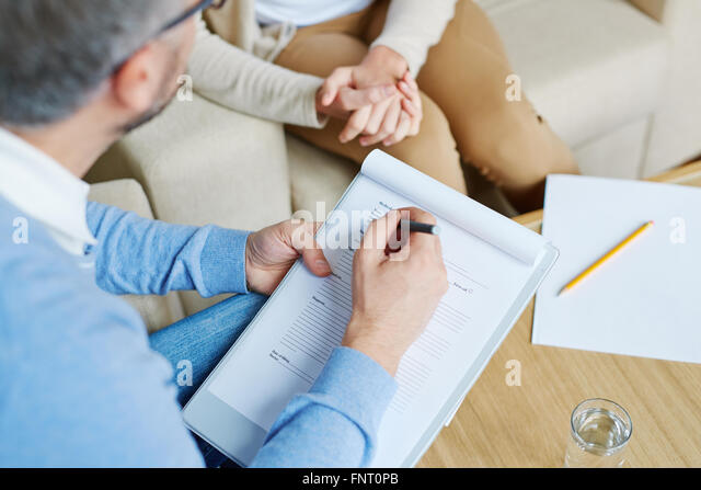 Psychologist talking to depressed woman in the office - Stock Image