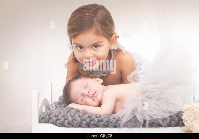 Portrait of a girl with newborn baby sister - Stock Image