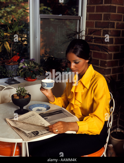 1970 1970s AFRICAN-AMERICAN WOMAN YELLOW BLOUSE SITTING TABLE BY WINDOW DRINKING MORNING COFFEE READING NEWSPAPER - Stock Image