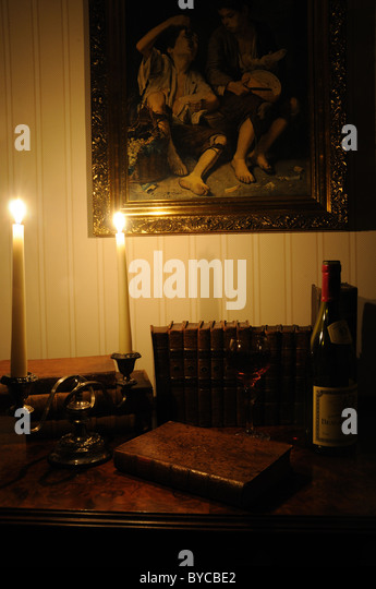 Antiquarian books and wine lit by candlelight - Stock-Bilder