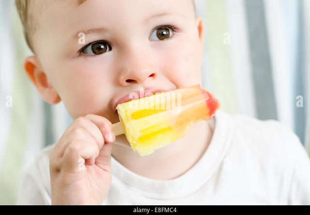 Baby boy eating ice lolly - Stock Image