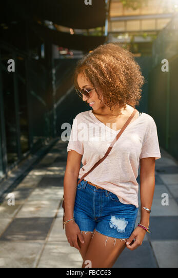 Young african american city girl. She is wearing casual outfit, sunglasses and looking down. - Stock Image