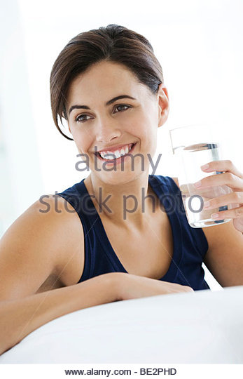Young woman with a glass of water on a sofa - Stock Image