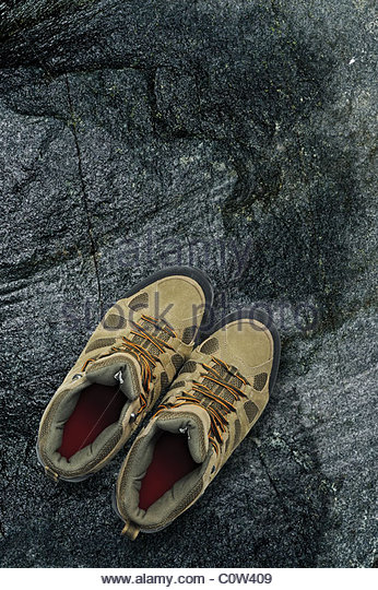 Walking boots on rock background - Stock Image