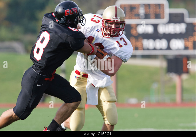 A Catholic University defensive back (l) tackles a Bridgewater College ball carrier (r) during a college football - Stock Image