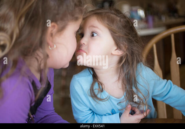 Sisters making faces at each other - Stock Image
