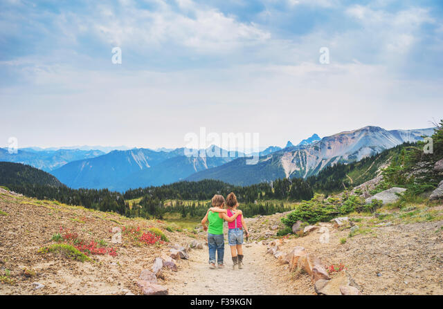 Rear view of Boy and girl  walking along a path with their arms around each other - Stock Image