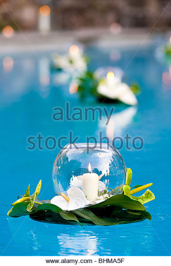 Candles in glass bowls floating on water - Stock Image