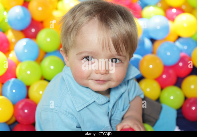 Baby playing in multi coloured balls - Stock Image