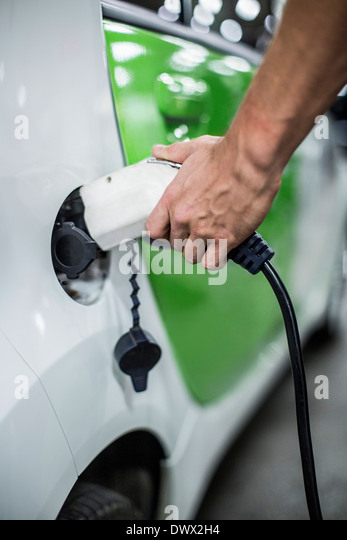 Cropped image of man charging electric car at gas station - Stock Image