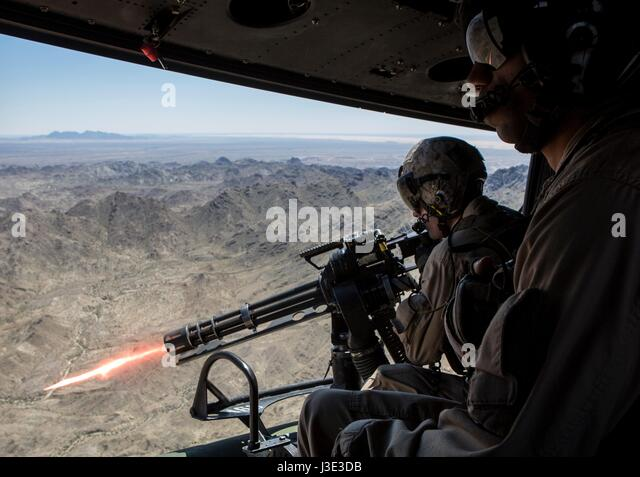 U.S. Marine soldiers fire a GAU-17 Vulcan Gatling machine gun cannon from a USMC UH-1Y Venom helicopter during an - Stock Image