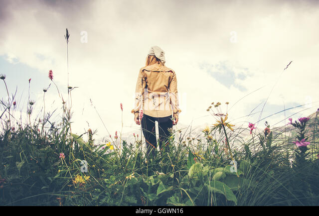 Young Woman walking alone Travel Lifestyle concept Summer vacations outdoor rocky mountains on background view from - Stock Image
